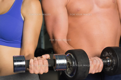 Mid section of a shirtless man and woman with dumbbellsの写真素材 [FYI00485828]
