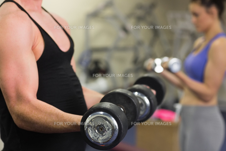 Man and woman using dumbbells in the gymの写真素材 [FYI00485831]