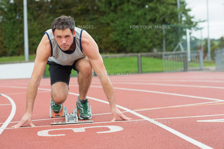 Young man ready to race on running trackの写真素材 [FYI00485833]