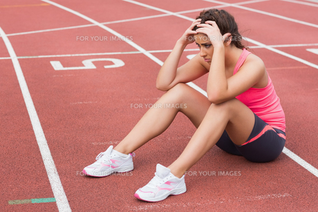 Young sporty woman sitting on the running trackの写真素材 [FYI00485835]