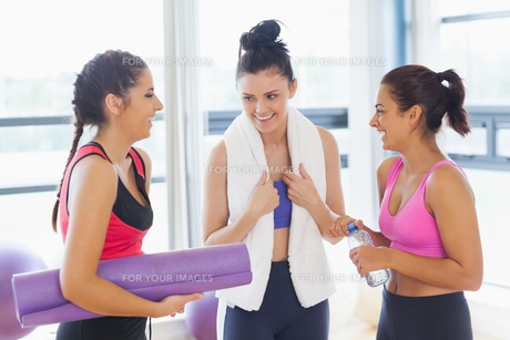 Three fit young women chatting in exercise roomの素材 [FYI00485837]