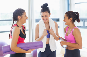 Three fit young women chatting in exercise roomの写真素材 [FYI00485837]