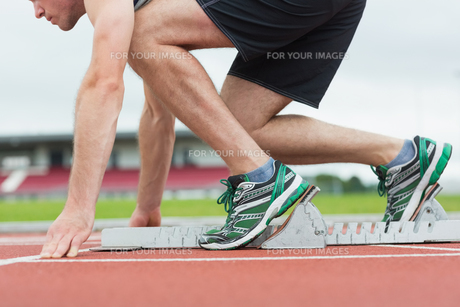 Side view of a man ready to race on running tracの写真素材 [FYI00485838]