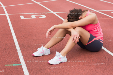 Tensed sporty woman sitting on the running trackの写真素材 [FYI00485841]
