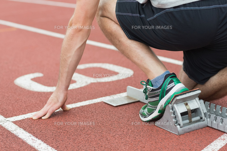 Mid section of a man ready to race on running trackの写真素材 [FYI00485844]