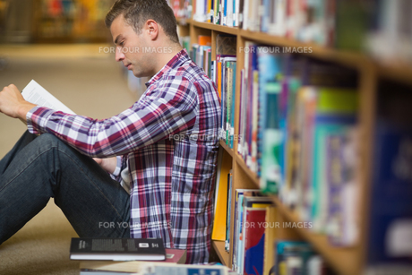 Focused young student sitting on library floor readingの素材 [FYI00485845]