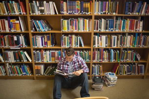 Concentrating young student sitting on library floor readingの写真素材 [FYI00485846]