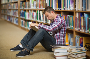 Student sitting on library floor readingの写真素材 [FYI00485847]