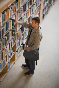 Student taking a book from shelf in libraryの素材 [FYI00485849]