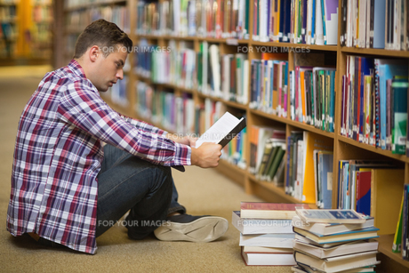 Handsome young student sitting on library floor reading bookの素材 [FYI00485851]