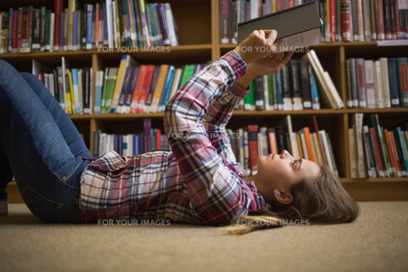 Pretty student lying on library floor reading bookの写真素材 [FYI00485859]