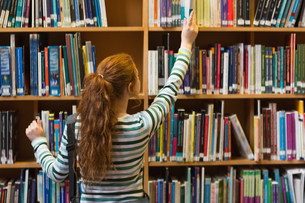 Redhead student taking book from top shelf in libraryの素材 [FYI00485863]