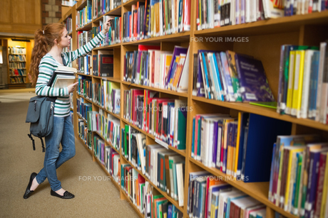 Redhead student taking book from shelf in the libraryの写真素材 [FYI00485865]