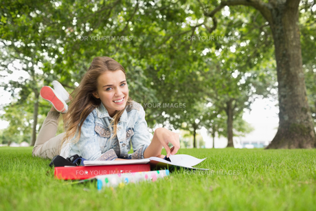 Happy young student lying on the grass studyingの写真素材 [FYI00485866]