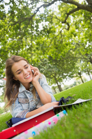Young happy student lying on the grass on the phoneの写真素材 [FYI00485867]