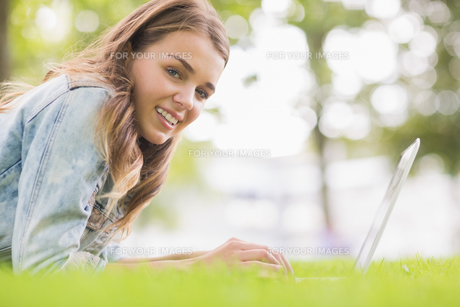 Happy student lying on the grass using her laptop looking at cameraの写真素材 [FYI00485870]