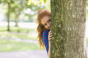 Cute redhead hiding behind a treeの写真素材 [FYI00485873]