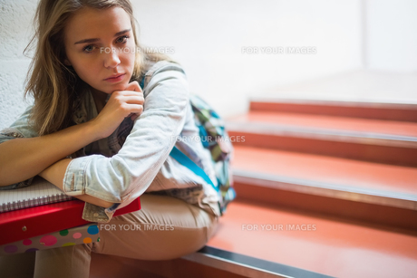 Sad lonely student sitting on stairs looking at cameraの写真素材 [FYI00485875]