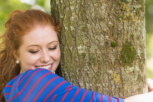 Smiling redhead hugging a treeの写真素材 [FYI00485876]