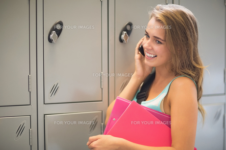 Pretty student talking on the phone beside lockersの写真素材 [FYI00485887]