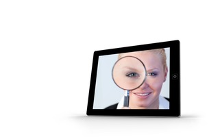 Businesswoman holding magnfying glass on tablet screenの素材 [FYI00485943]