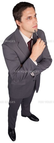 Thinking businessman holding penの写真素材 [FYI00485950]