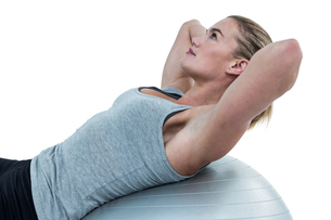 Muscular woman doing sit ups on exercise ballの写真素材 [FYI00486051]