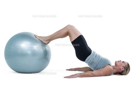 Muscular woman lying on floor with legsの写真素材 [FYI00486056]