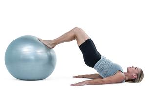 Muscular woman lying on floor with legsの素材 [FYI00486056]