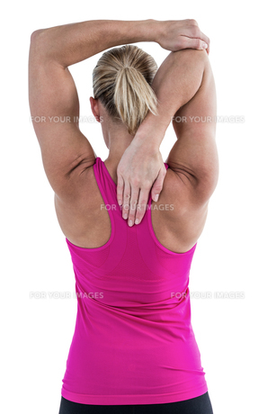 Rear view of muscular woman stretching her armの写真素材 [FYI00486058]