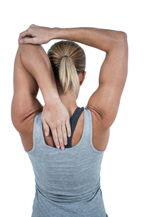 Rear view of muscular woman stretching her armの写真素材 [FYI00486059]