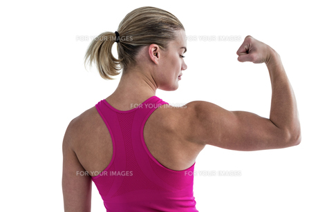 Rear view of muscular woman flexing musclesの写真素材 [FYI00486066]