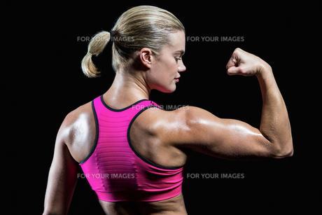 Muscular woman flexing her armの素材 [FYI00486069]