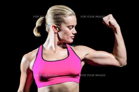 Muscular woman flexing her armの素材 [FYI00486071]