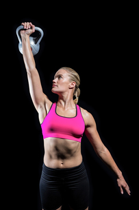 Muscular woman lifting heavy kettlebellの写真素材 [FYI00486078]