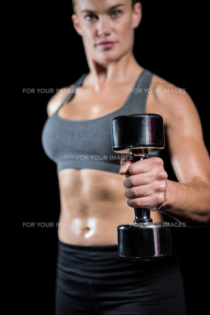 Muscular woman lifting heavy dumbbellsの写真素材 [FYI00486085]