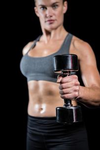 Muscular woman lifting heavy dumbbellsの素材 [FYI00486085]