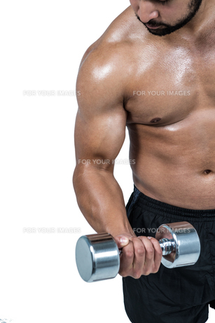 Muscular man lifting heavy dumbbellの写真素材 [FYI00486098]