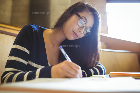 Focused student writing on notebookの写真素材 [FYI00486106]