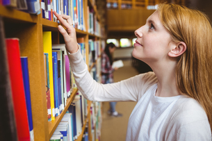 Blond student looking for book in library shelvesの写真素材 [FYI00486117]