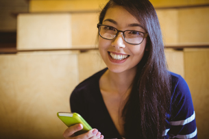Smiling student texting in lecture hallの写真素材 [FYI00486120]