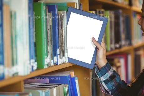 Pretty student putting table in bookshelfの写真素材 [FYI00486123]