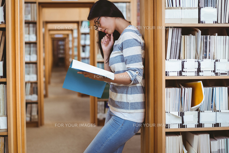 Focused student leaning against bookshelves and reading a book in libraryの素材 [FYI00486125]