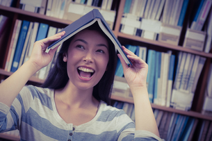 Funny student holding book on her headの写真素材 [FYI00486127]