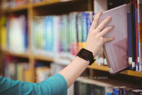 Students hand with smartwatch picking book from bookshelfの写真素材 [FYI00486131]