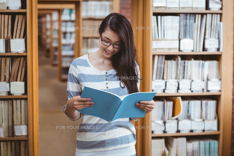 Pretty student reading a book in libraryの写真素材 [FYI00486133]