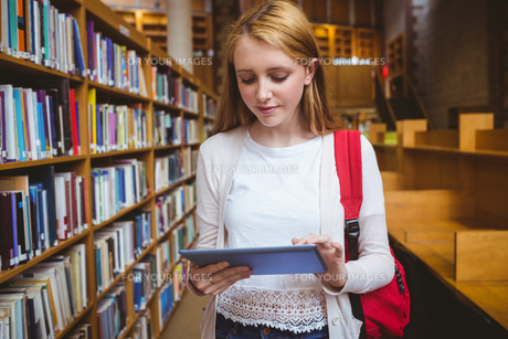 Blond student with backpack using tablet in libraryの写真素材 [FYI00486134]