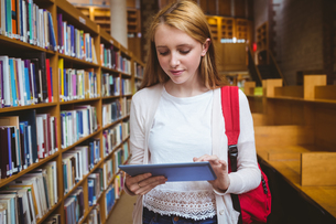 Blond student with backpack using tablet in libraryの素材 [FYI00486134]