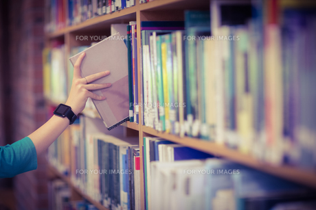 Students hand with smartwatch picking book from bookshelfの写真素材 [FYI00486138]