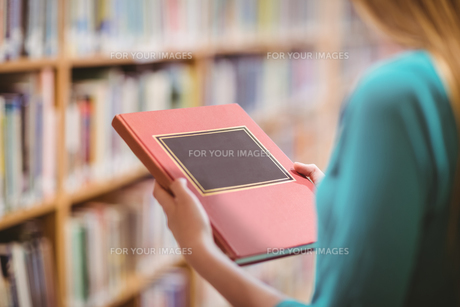 Over shoulder view of student in library holding bookの写真素材 [FYI00486144]